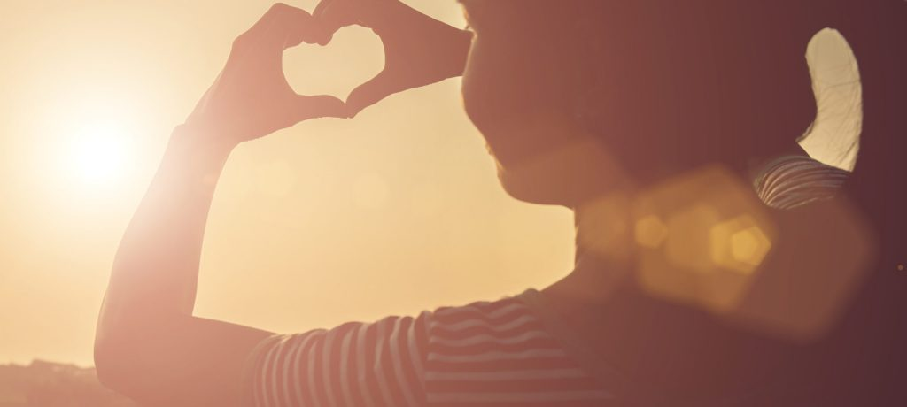 Young woman hands shaped heart against beautiful sunset.